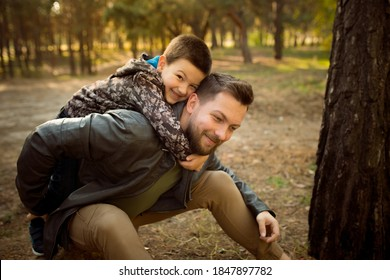 Hugging. Father and son walking and having fun in autumn forest, look happy and sincere. Laughting, playing, having good time together. Concept of family, happiness, holidays, childhood, lifestyle.