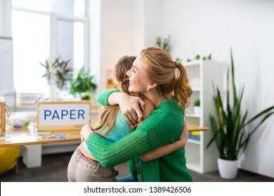 Hugging girl. Beaming blonde-haired teacher feeling happy while hugging smart hard-working girl