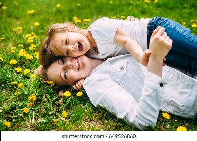 hugging happy mother and daughter for a walk in the park On the green lawn