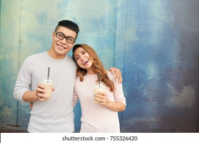 Hugging happy young Vietnamese couple drinking milkshakes
