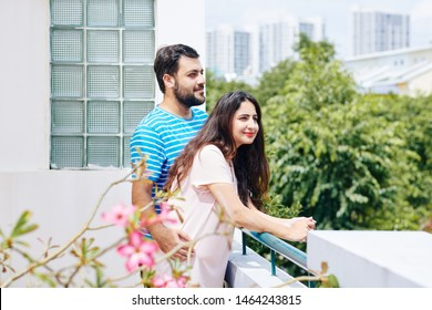 Hugging positive Indian couple enjoying view from the balocony of their new apartment or hotel room
