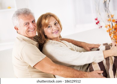 Hugging Senior couple sitting in living room.