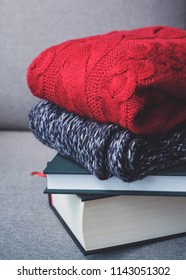 huggy autumn winter concept, red sweaters and books on grey background, cold weather, cozy home