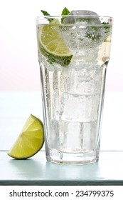 Hugo cocktail with lime, mint and ice cubes, close up