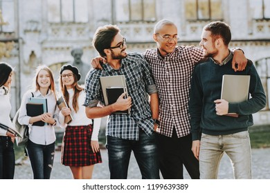 Hugs. Guys. Books. Standing in University. Good Mood. Intelligence. Standing Together. Outside. Sunny Day. Students. Holding Friends. Happy. Students. Courtyard. Books. University. Knowledge.