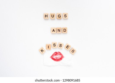 Hugs and kisses words on white marble background