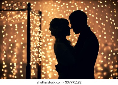 hugs lovers in silhouette against the background of garlands of lights