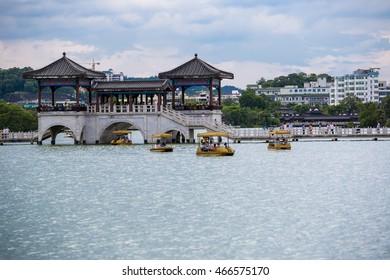 HUIZHOU, CHINA - 26 JULY 2014: Peddle boats and vintage bridge structure at Huizhou west lake recreation park, Huizhou, Guangdong, China.