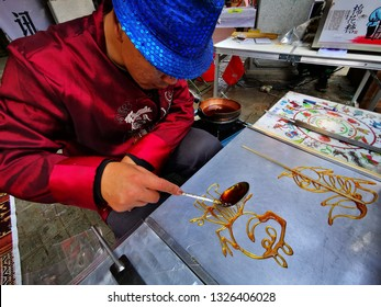 """Huizhou, China - FEB 2019: Folk artist are making traditional Chinese snacks """"sugar paintings"""" on the spot for Peppa Pig"""