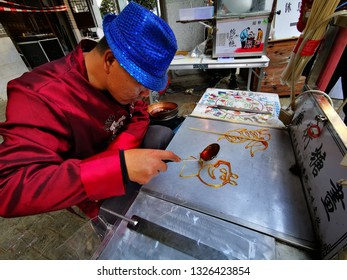 "Huizhou, China - FEB 2019: Folk artist are making traditional Chinese snacks ""sugar paintings"" on the spot for Peppa Pig"