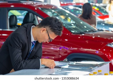 Huizhou, China - MAR 2019: A car salesman was boring to play with his mobile phone at the auto show because he had no inquiries from customers.