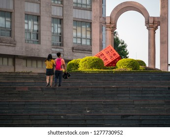 """Huizhou, China - OCT 2017: The lovers are walking in Xiapu Riverside Park, Huicheng District, a red statue of """"socialist core values"""" in the center of the flower garden."""