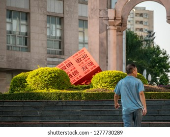 """Huizhou, China - OCT 2017: The man walking in Xiapu Riverside Park, Huicheng District, a red statue of """"socialist core values"""" in the center of the flower garden."""