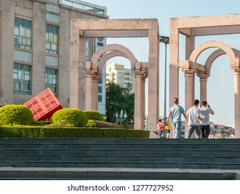 """Huizhou, China - OCT 2017: The people are walking in Xiapu Riverside Park, Huicheng District, a red statue of """"socialist core values"""" in the center of the flower garden."""