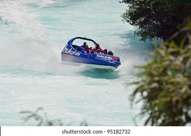 HUKA FALLS, NEW ZEALAND - JANUARY 28: A fast jet boat  with tourists races near Huka Falls in Taupo, New Zealand on January 28, 2012.