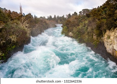Huka Falls on the Waikata River, Wairakei National Park, New Zealand. Raging torrent flows through tree lined gorge with cloudy sky