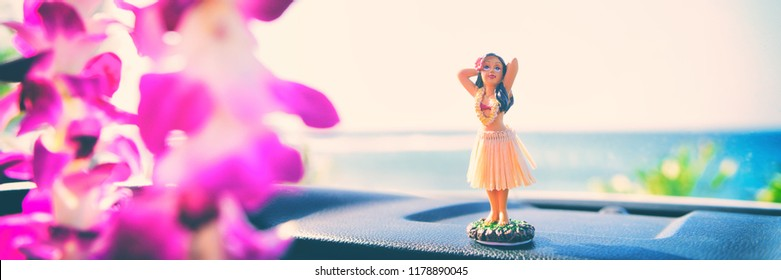 Hula car dashboard road trip Hawaii dancer doll - girl dancing on summer holiday vacation in Maui. with purple flowers lei hanging from mirror. Banner panorama.