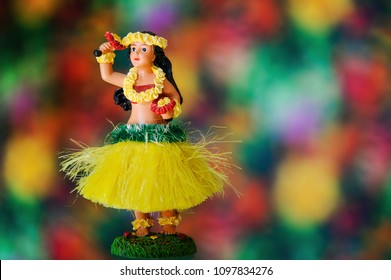 Hula dance girl doll wearing traditional Hawaiian costume over colorful background with free space for text