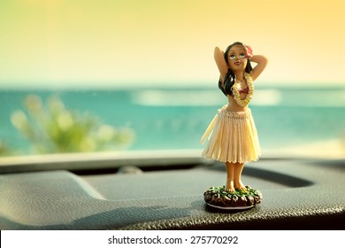 Hula dancer doll on Hawaii car road trip. Doll dancing on the dashboard in front of the ocean. Tourism and Hawaiian travel freedom concept.