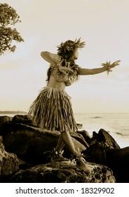 Hula dancer on rocks by ocean