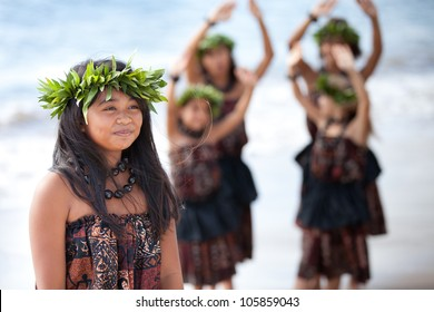 Hula girl on the beach with her fellow dancers behind her