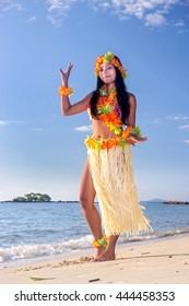Hula Hawaii dancer dancing on the sea beach with blue background. Beautiful woman in a Hawaiian costume on the tropical coast of island.