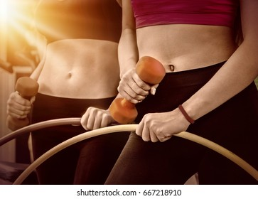 Hula hoop woman and people with dumbbells and hoops his body at gym. Cropped shot of bare female belly . Color sepia tone on shiny sunlight background.