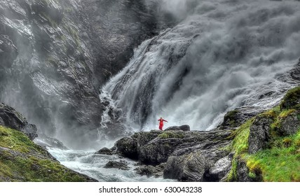 A Huldra (seductive forest creature) dances in front of the Kjosfossen waterfalls near to flam, Norway in summertime