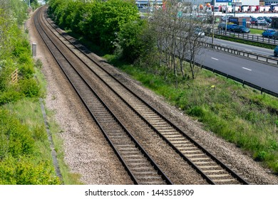 Hull, UK - 12 May 2019: The train track from Hull train station alongside Clive Sullivan Way motorway near Hull city centre with yellow train driving and cars passing on the busy road.