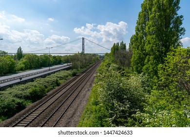 Hull, UK - 12 May 2019: The train track from Hull train station alongside Clive Sullivan Way motorway near Hull city centre with yellow train and the Humber Bridge single span bridge in the background