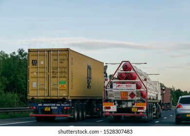 Hull, UK - 23 August 2019: Lorry truck overtaking on British motorway. Slow accelerating lorries cause traffic congestion and slows down commuters on highways. Highway code, pollution, traffic concept