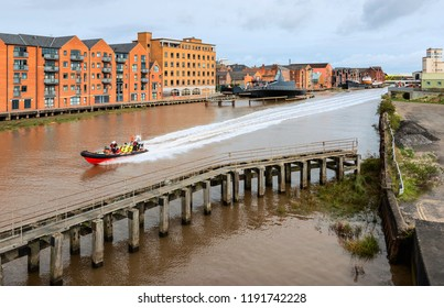HULL, UK - SEPTEMBER 30, 2018: Humber Rescue inflatable speeds down River Hull flanked by modern flats and offices and derelict causeway on September 30, 2018 in Hull, Yorkshire, UK.