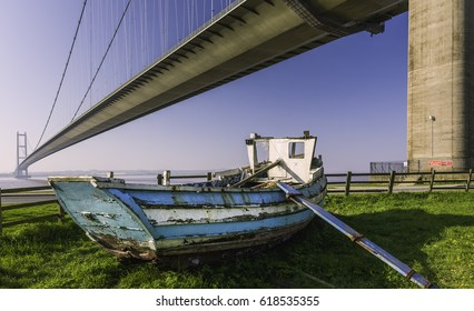 Hull, Yorkshire, UK. A derelict wooden boat under the Humber Bridge which spans the Humber estuary and viewed on a spring morning in Hessle, near Hull, Yorkshire, UK.
