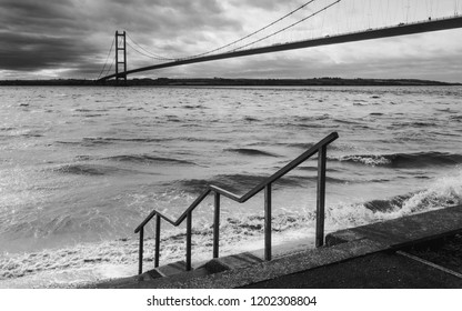 Hull, Yorkshire, UK. View across the Humber estuary with the Humber bridge in the background  with stormy sky in autumn near Hull, Yorkshire, UK.