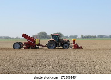Hulst, Holland - apr 4, 2020: a tractor with a potato planter is planting potatoes in the fields with a lot of dust because of drought in springtime in the dutch countryside