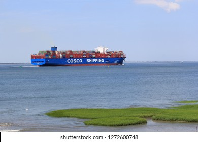 HULST, HOLLAND - JUL 23, 2018: cargo ship cosco shipping navigates through the sea along the green salt marsh towards antwerp at a summer day