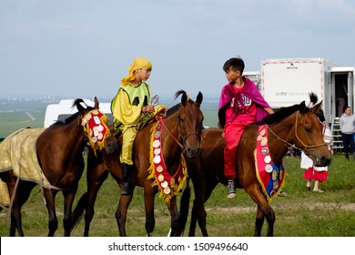 Hulunbuir, Inner Mongolia / China - Aug 09 2019: A scene of Mongolian kids. They are preparing for horse racing,  as one of sports in Nadam Fair (a Mongolian traditional festival).