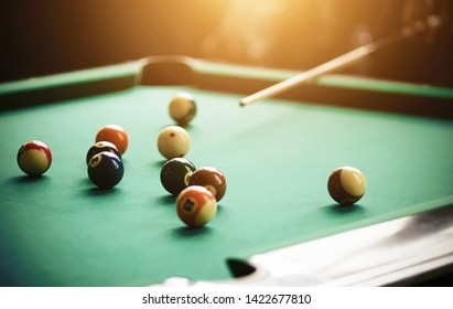 A human aims a cue at billiard balls of different colors lying on a green billiard table.
