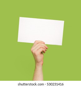 Human Arm Holding white paper isolated on green Background