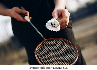 A human in black clothes holding a racket and is going to throw a shuttlecock. A pleasant outdoor activity is playing badminton on a Sunny day.