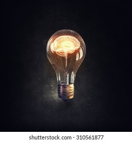 Human brain glowing inside of light bulb on dark background