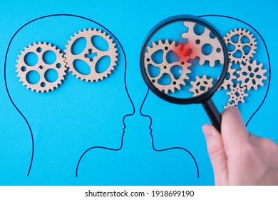Human brain is made gear mechanism on blue background. The brain is viewed through a magnifying glass. Brain damage concept.
