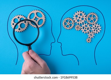 Human brain is made gear mechanism on blue background. The brain is viewed through a magnifying glass. Two different thought processes, concept of different thinking.