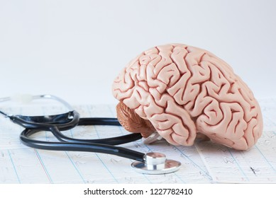 Human brain model and a black stethoscope on background of brain waves from electroencephalography