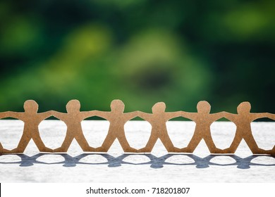 Human chain paper setup at outdoor in sunlight with blurred green forest on background