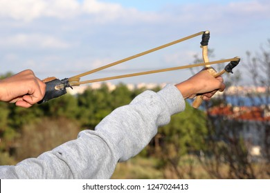 human (child) is throwing stone with slingshot - wooden slingshot with a stretched rubber band. slingshot is ready to fire