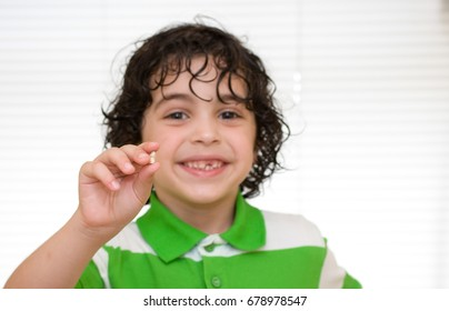 Human development stage: Child holding a baby tooth that has just dropped over white background. He is happy smiling.