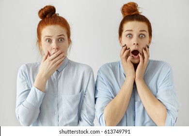 Human emotions and feelings. Face expressions. Two red haired astonished Caucasian students looking like twins with hair knots dressed in shirts. Bug-eyed sisters learned shocking information