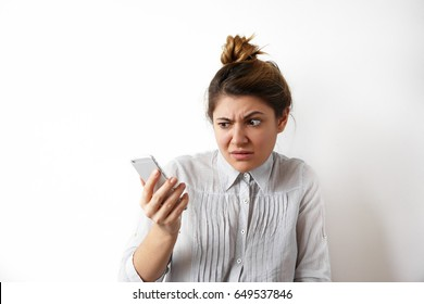 Human emotions, feelings and reactions. Attractive young woman with hair bun looking at mobile phone seeing bad news photos having scared or shocked facial expression, raising eyebrows