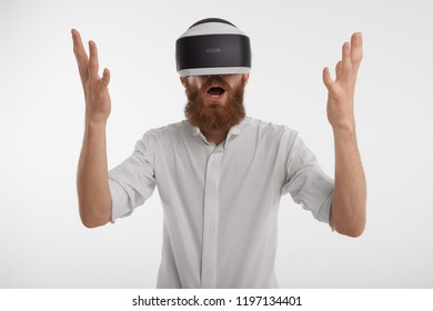 Human emotions and modern technologies. Portrait of emotional male office worker in formal shirt exclaiming and raising hands being fascinated and shocked, wearing virtual reality oculus rift headset